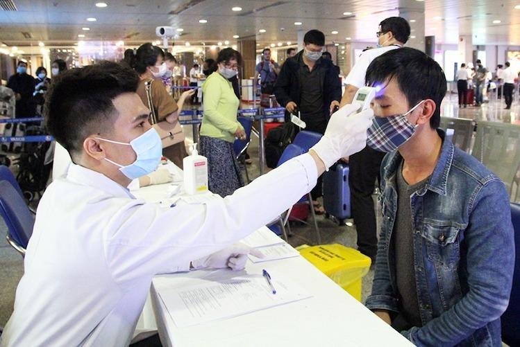 Nhân viên Trung tâm Kiểm dịch quốc tế đo thân nhiệt hành khách tại sân bay Tân Sơn Nhất. Ảnh: Hữu Nguyên.