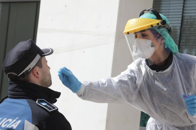 Một cảnh sát bị kiểm tra bằng gạc bông tại tòa thị chính Madrid. Ảnh: AFP.