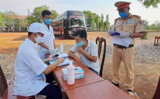 Các tài xế khai báo y tế khi qua các chốt kiểm soát. Ảnh: T. N.
