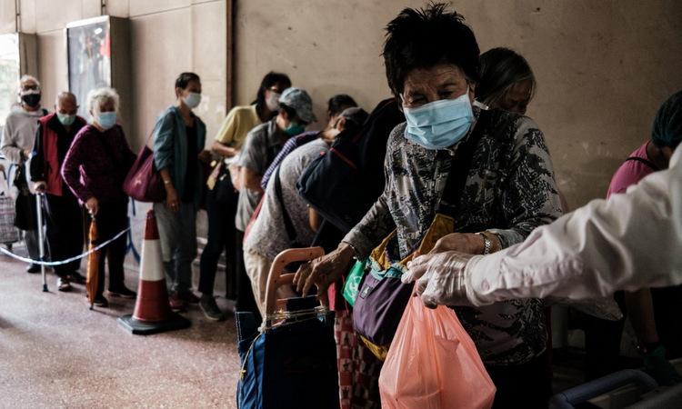 Người cao tuổi Hong Kong nhận đồ ăn miễn phí hôm 27/3. Ảnh: AFP.