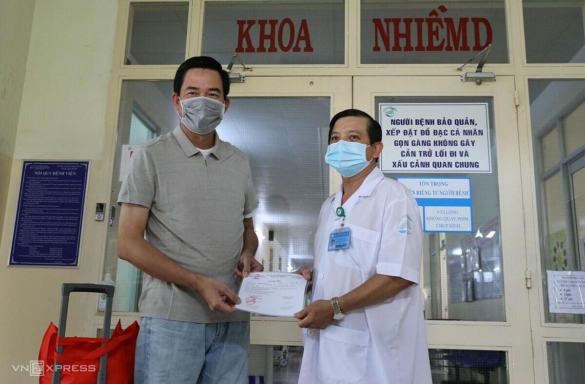 Bác sĩ Nguyễn Thanh Phong (bên phải) trao giấy ra viện cho bệnh nhân 150 chiều 7/4. Ảnh: Quỳnh Trần.