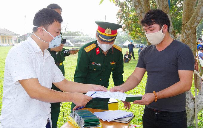 Người dân (bên phải) nhận giấy chứng nhận hoàn thành cách ly. Ảnh: Văn Đức.