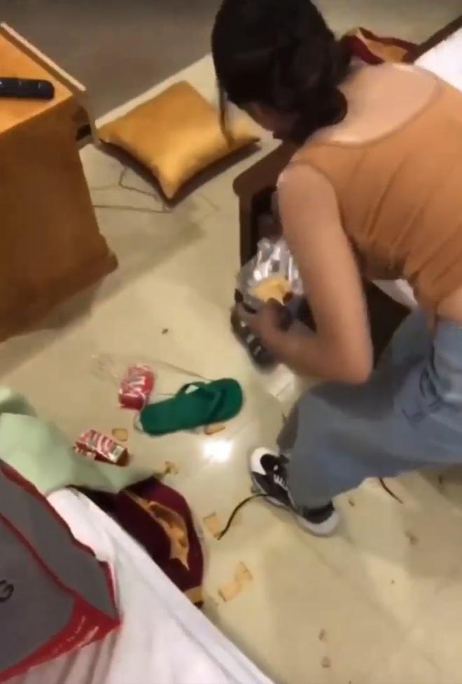 Cô gái bẻ bánh vứt trên sàn nhà khách sạn. Ảnh chụp màn hình.