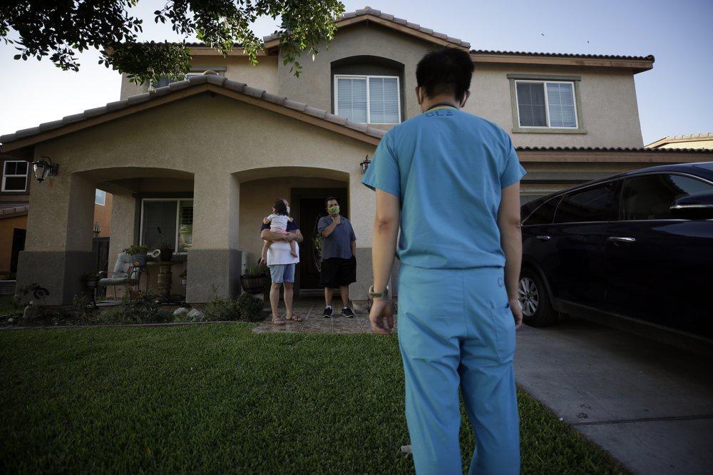 Bác sĩ Tien Vo tới khám một gia đình nhiễm Covid-19, phải cách ly tại nhà, ngày 23/7. Ảnh: AP.