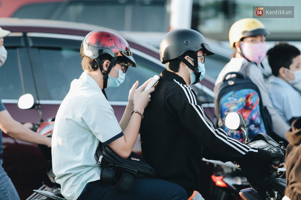 Một nam học sinh bấm điện thoại trong lúc đường phố kẹt xe.
