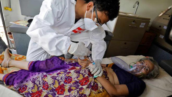 Một bác sĩ chăm sóc một bệnh nhân có vấn đề về hô hấp trong xe cấp cứu đang chờ nhập viện để điều trị trong bối cảnh dịch bệnh đang lan rộng ở Ahmedabad, Ấn Độ ngày 25/4/2021. Ảnh: Amit Dave /Reuters