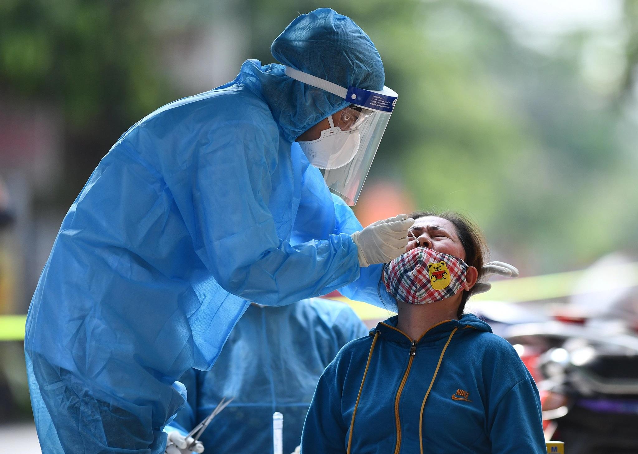 Lực lượng chức năng lấy mẫu xét nghiệm SARS-CoV-2 cho người dân hẻm 77, quận Bình Tân (TP.HCM) vì liên quan ca mắc Covid-19. Ảnh: Phạm Ngôn.