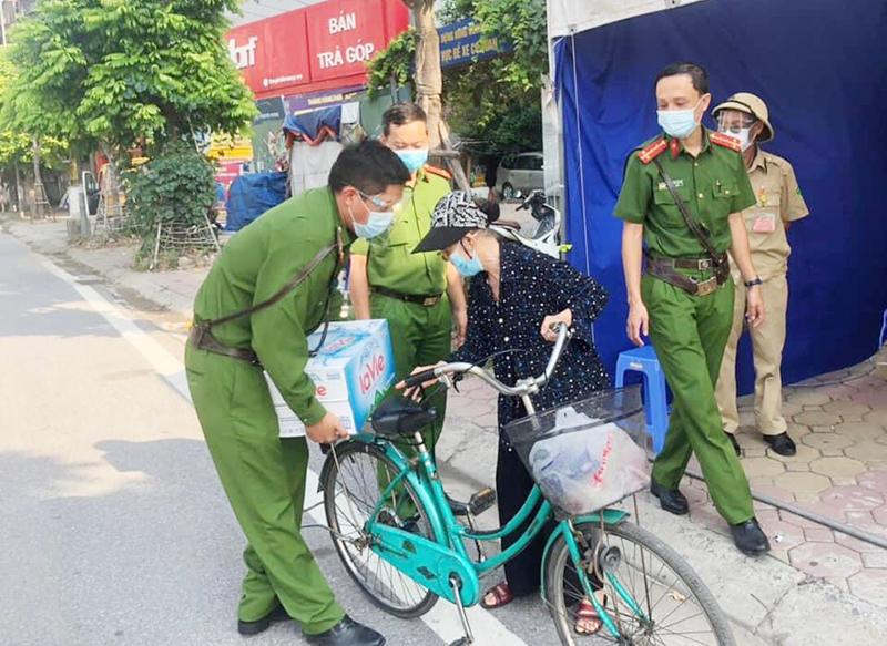 Cụ bà đạp xe chở nước tiếp sức cho cán bộ phòng chống dịch Covid-19 ở điểm chốt 86 đường Trường Chinh.